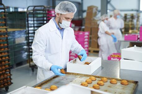 Mann mit Arbeitshandschuhen in der Lebensmittelindustrie