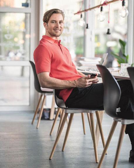 Mann sitzt auf schwarzem Besucherstuhl im Pausenraum und blickt in die Kamera