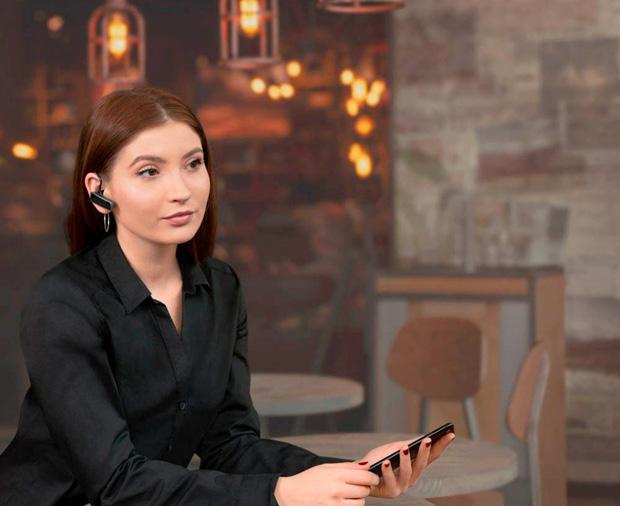 Frau kommuniziert über ein Bluetooth-Headset mit ihrem Smartphone