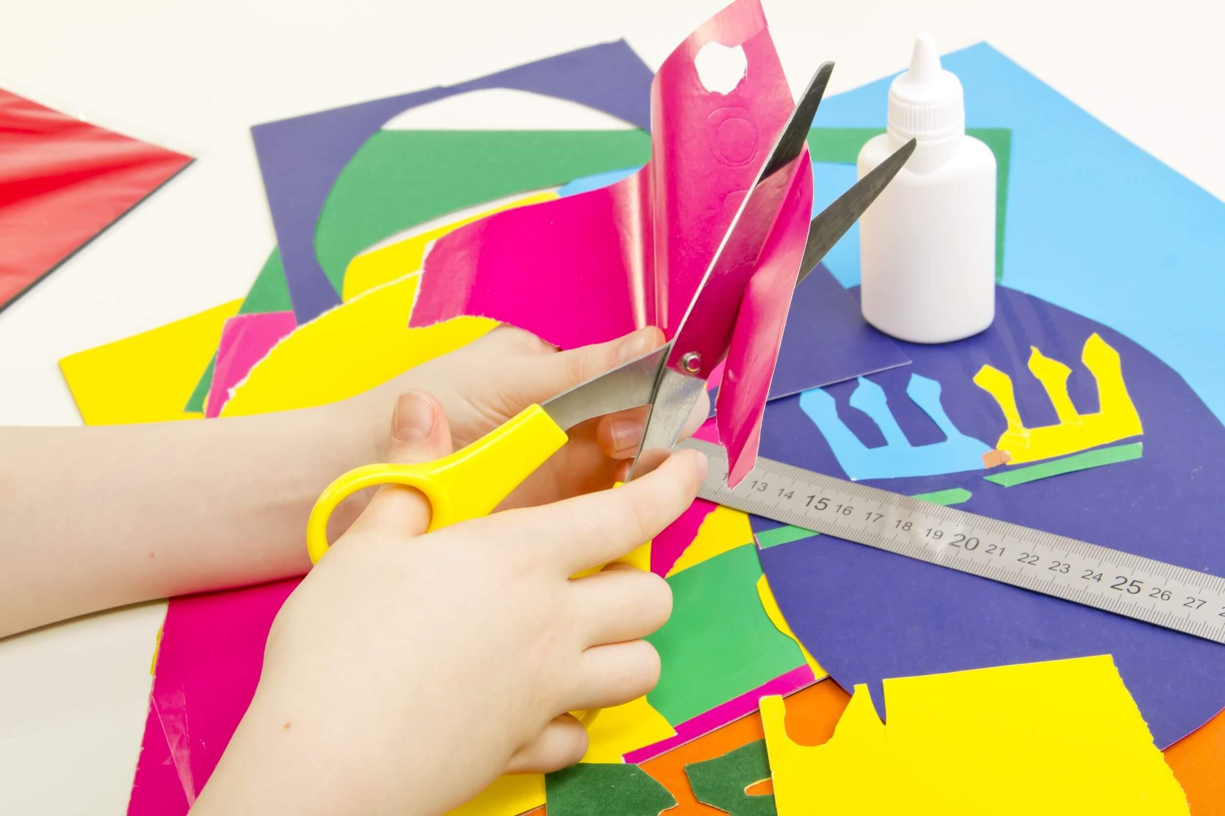 Eine Kinderhand, die mit einer Schere Formen aus buntem Papier ausschneidet