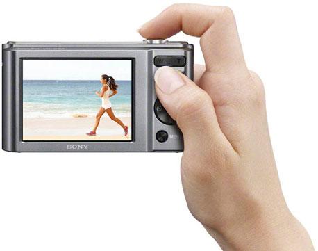 Eine Hand hällt eine Digitalkamera und drückt den Auslöser