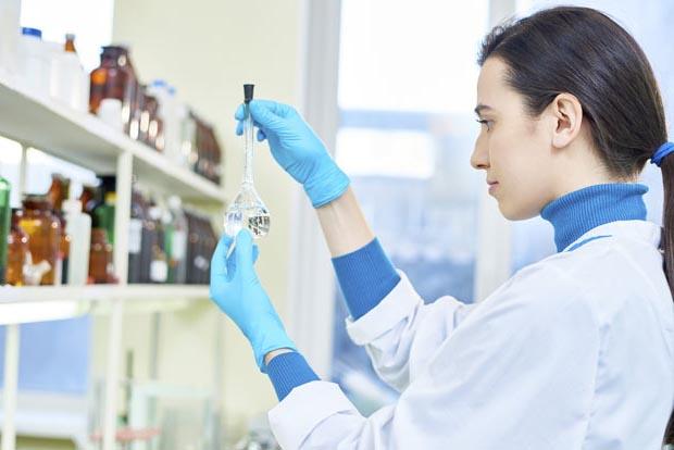 Laborantin trägt blaue Einmalhandschuhe