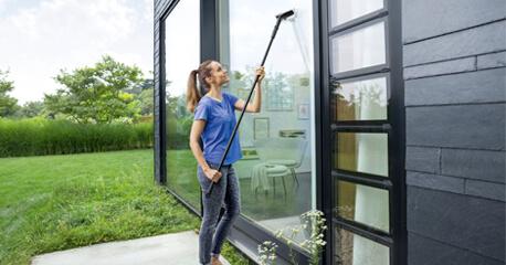 Junge attraktive Frau reinigt mit einem Fenstersauger eine Glasdusche