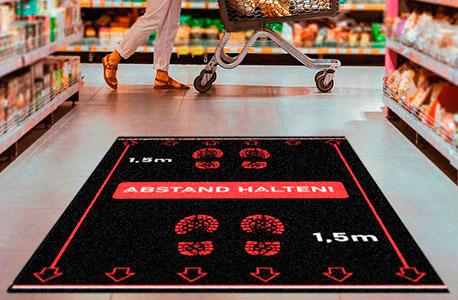 Fußmatte im Supermarkt mit der Aufschrift Bitte Abstand halten