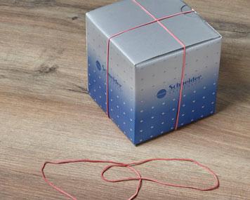 Zwei Gummiringe verschließen eine Schachtel und zwei weitere liegen davor
