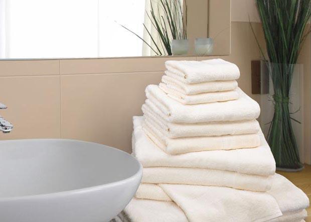 Gestapelte Handtücher in verschiedenen Größen neben einem Waschbecken liegend