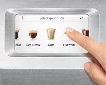 Zeigefinger drückt auf Display eines Kaffeevollautomaten