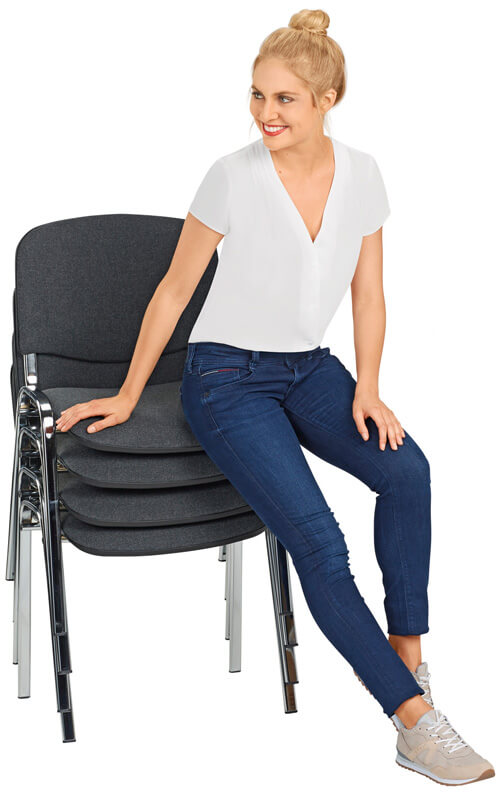 Model sitzt auf vier gestapelten Stühlen