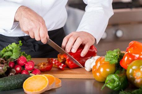 Koch schneidet Paprika mit einem Kochmesser in Scheiben