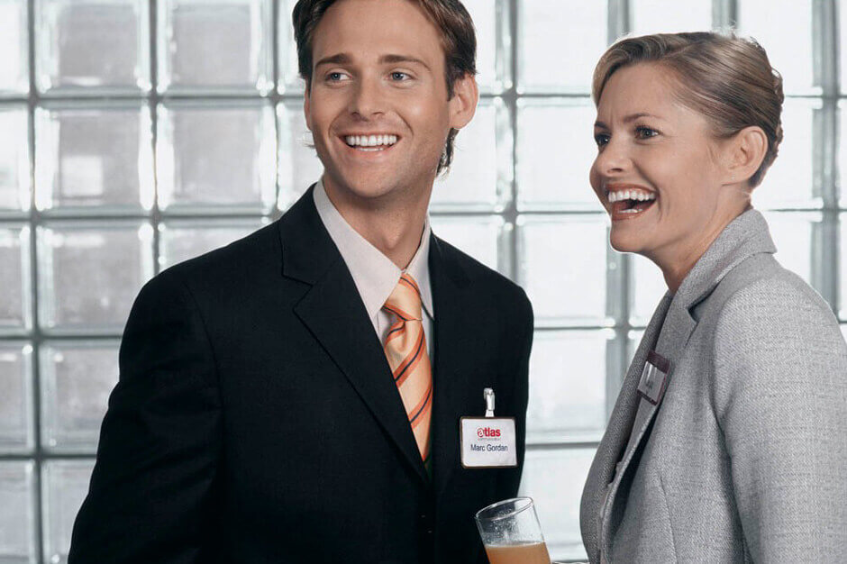 Mann trägt ein Namensschild und unterhält sich mit einer Frau