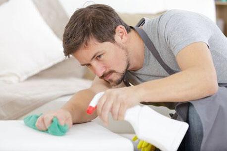 Mann reinigt weiße Polstermöbel