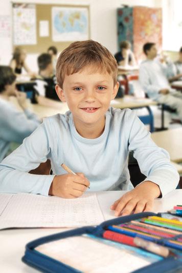 Junge schreibt in der Schule in ein karrierte Schulheft