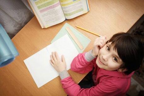 Kind sitzt am Schreibtisch mit Schulheft auf dem Tisch und schaut lächelnd in die Kamera