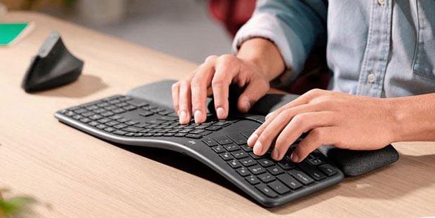 Mann tippt auf einer ergonomisch geschwungenen Tastatur
