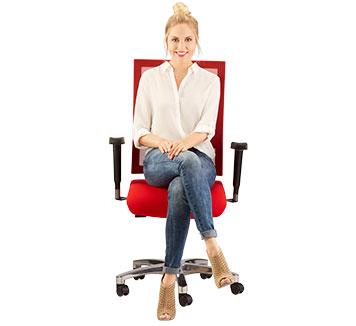 Freundlich lächelnde Frau sitzt auf einem Bürostuhl